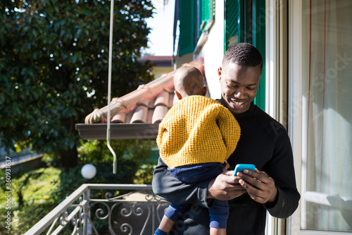 Daddy holding his child in his arms using smartphone - Single parent watching vi Canvas-taulu