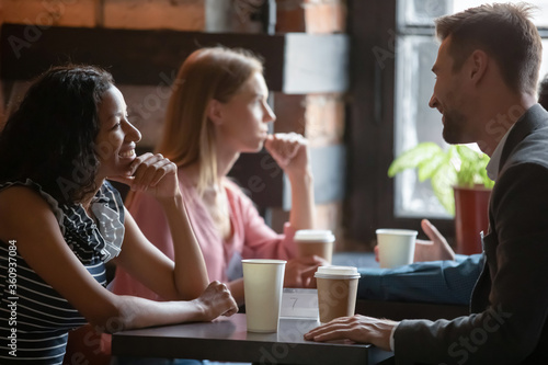 Fotografia Multi ethnic couples sitting in cafe enjoy chatting, focus on African girl flirting with Caucasian guy during speed dating romantic meeting participation
