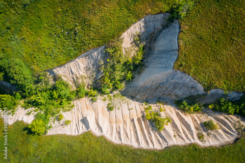 Fotografie, Obraz Chalk crevice or ravine among green grass meadow hills, aerial top view, abstract nature background