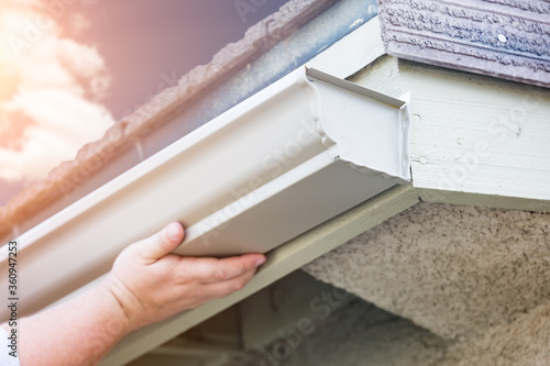 Photo Worker Attaching Aluminum Rain Gutter to Fascia of House
