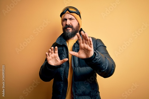 Fototapeta Handsome skier bald man with beard skiing wearing snow sportswear and ski goggles disgusted expression, displeased and fearful doing disgust face because aversion reaction