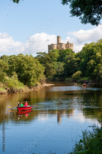 Fototapeta Rowing boats on the River Coquet with Warkworth Castle in the background on a su