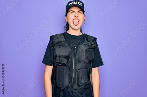Fotografía Young police woman wearing security bulletproof vest uniform over purple background sticking tongue out happy with funny expression