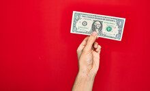 Beautiful Hand Of Man Holding One Dollar Banknote Over Isolated Red Background
