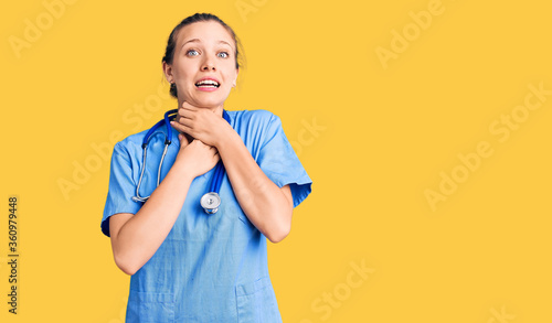 Young beautiful blonde woman wearing doctor uniform and stethoscope shouting and suffocate because painful strangle Wallpaper Mural