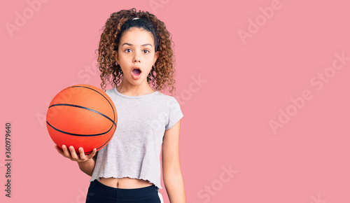 Beautiful kid girl with curly hair holding basketball ball scared and amazed wit Wallpaper Mural