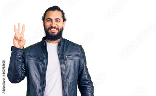 Young arab man wearing casual leather jacket showing and pointing up with fingers number three while smiling confident and happy Wallpaper Mural