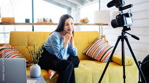 Valokuvatapetti Handsome casual woman sitting on the couch and filming video blog