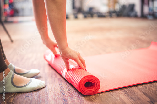 Fototapeta Cropped image of woman rolling yoga mat. Time for meditation. Healthy lifestyle. obraz