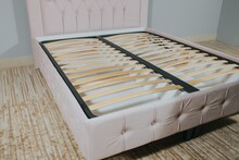 Closeup Shot Of A Bed With Pink Fabric Upholstery And A Wooden Frame Without Mattress