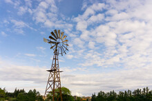 The Old Rusting Steel Windmill Is A Machine For Producing Continuous Power From Wind And Air, In Which A Wheel Fitted With Steel Vanes, Trees In The Background Under White Fluffy Cloudy And Blue Sky