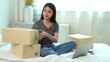 Asian women write on paper boxes, Online purchase and delivery.