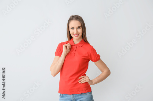 Fotomural Beautiful young woman in stylish polo shirt on light background