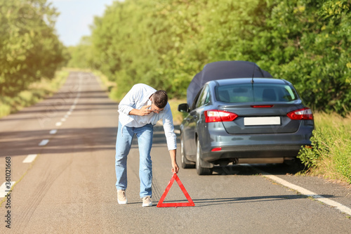 Canvastavla Young man with emergency stop sign near broken car on road