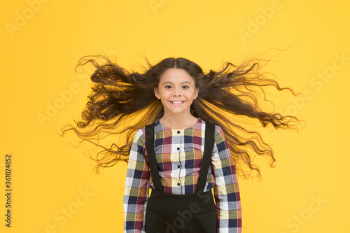 Extra light. Air in her hair. natural beauty. Girl kid long hair flying in air. Child with natural beautiful healthy hair yellow background. Tips for healthy hair. Hairdresser salon. Beauty procedure