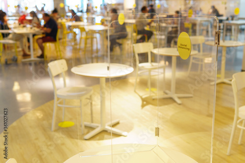 Fototapeta Cleary acrylic / plastic divider or barrier on table in food court as part of safety protection for customers. Reopen, New normal & Social distancing during Covid-19 pandemic obraz