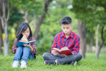 Brother And Sister Sitting On The Grass And Reading The Book In The Park, Kids Playing & Outdoor Learning Concept