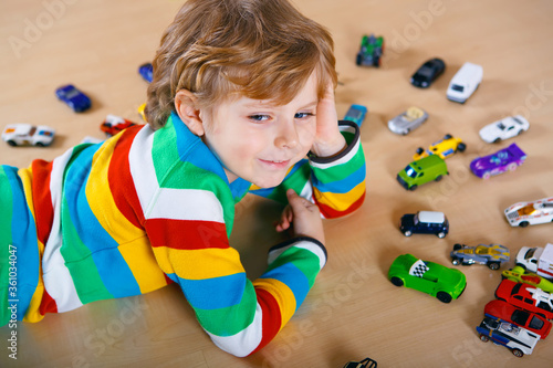 Lovely blond kid boy playing with lots of toy cars indoor. Happy healthy child boy having fun during pandemic coronavirus quarantine disease. Child alone at home, closed nursery.