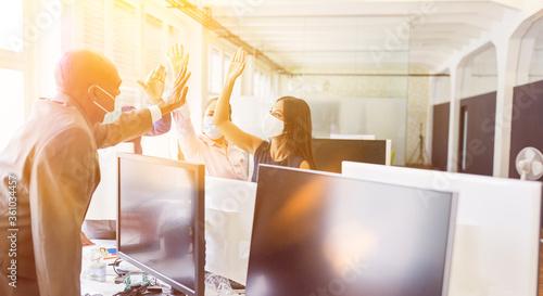 Photo Geschäftsleute im Büro mit Mundschutz machen High Five