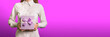 Leinwanddruck Bild - A young girl holds a gift box on a purple background. The face of the girl is not visible. The concept of surprise