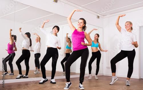Billede på lærred Cheerful different ages women learning swing steps at dance class