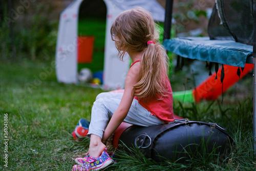 Fillette blonde dans un jardin enlève ses chaussures pour jouer plein air Canvas Print