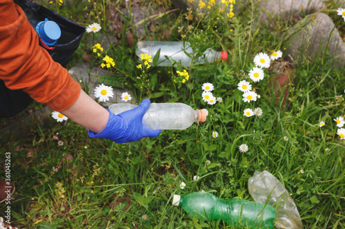 Fototapeta volunteer young woman collecting garbage and picking up plastic bottle waste at