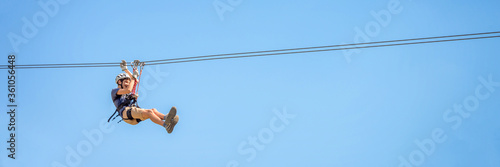 Tela Teenager having fun on a zipline on panoramic blue sky background with copy space