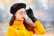 Beautiful Fashionable Girl In A Yellow Sweater And Black Beret With Sunglasses On Her Face Against A Blurred Colored Wall.