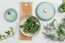 Teal Cast Iron Pot With Spinach, Fennel And Herbs On White Linen And Oak Board
