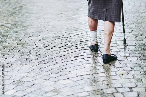 Femme âgée blessée à la jambe qui marche dans la rue avec un parapluie canne Canvas Print