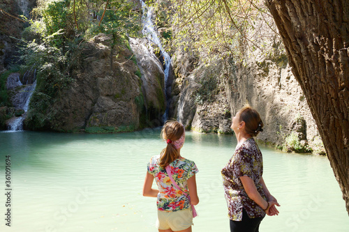 grandmother and granddaughter admire mountain waterfall Canvas Print