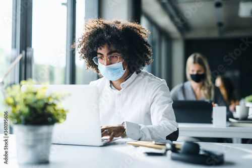 Portrait of young man with face mask back at work in office after lockdown. - 361095606