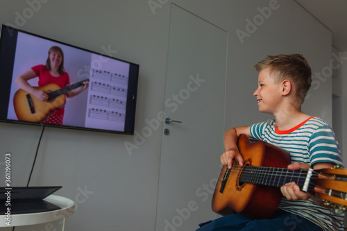 Vászonkép happy kid having guitar lesson online