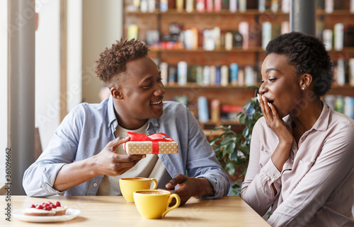 Fotografía Caring boyfriend surprising his girlfriend with unexpected gift at coffee shop