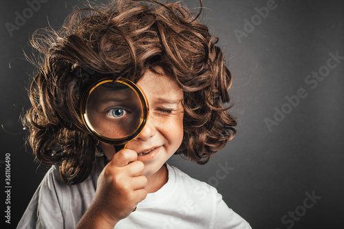 Child see through magnifying glass on the black backgrounds. Big kid eye #361106490
