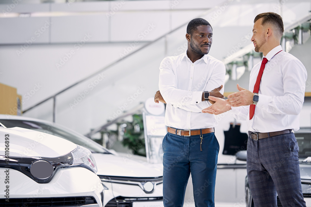 Fototapeta confident professional salesman talk about characteristics of car to customer man, black business man want to get necessary information about auto before making purchase, he asks questions