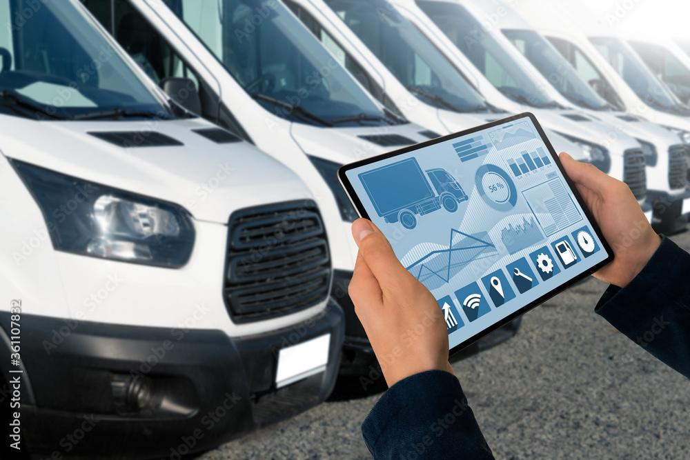 Fototapeta Manager with a digital tablet on the background of vans. Fleet management