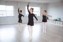 Caucasian Female Ballet Dancers In Black Suits Practicing During A Class In A Bright Studio
