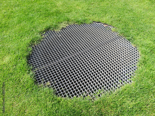 round metal grid in a grass field above an airshaft Canvas Print