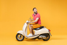 Side View Of Excited Young Bearded Man Guy In Casual Summer Clothes Driving Moped Isolated On Yellow Background In Studio. Driving Motorbike Transportation Concept. Mock Up Copy Space. Looking Aside.
