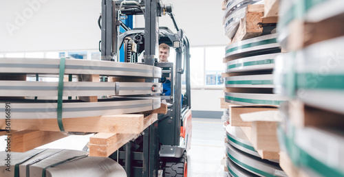 Fototapeta Worker transporting metal material from warehouse to production obraz