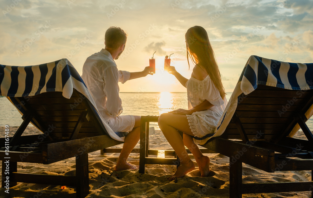 Fototapeta couple drinking cocktails on beach during vacation or honeymoon in tropics