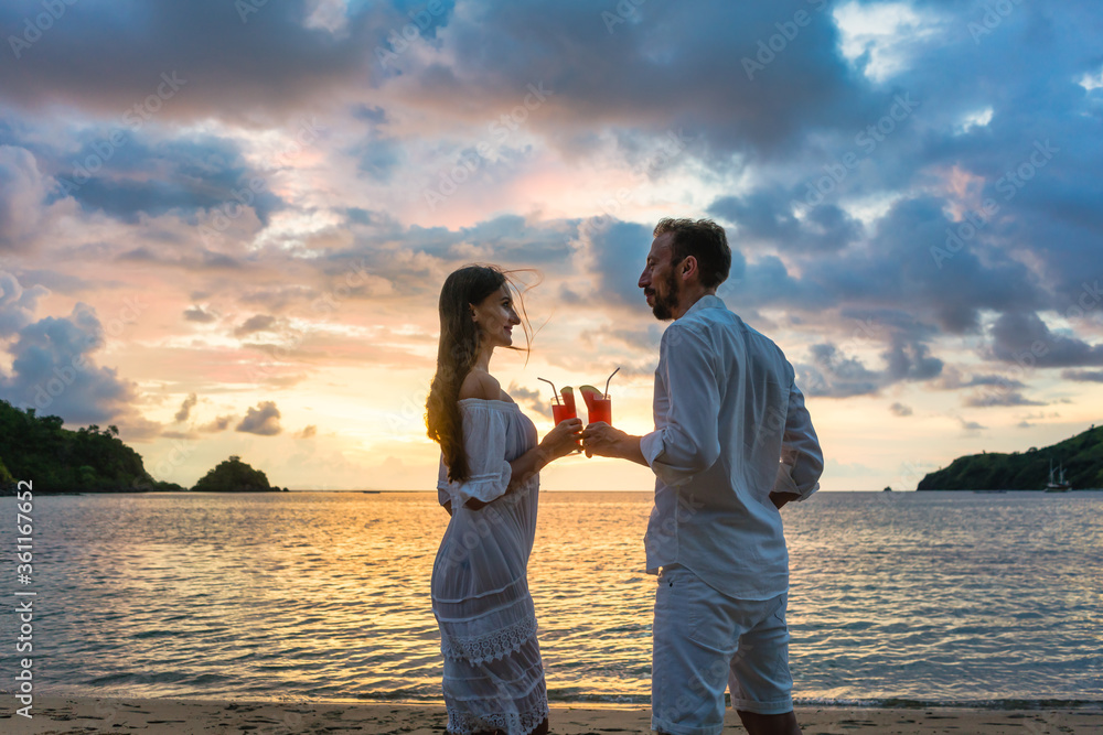 Fototapeta Couple in tropical vacation with drinks toasting on beach by the sea