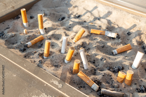 Photo Paris – France, August 19,2018 : Cigarette butts in an ashtray with sand