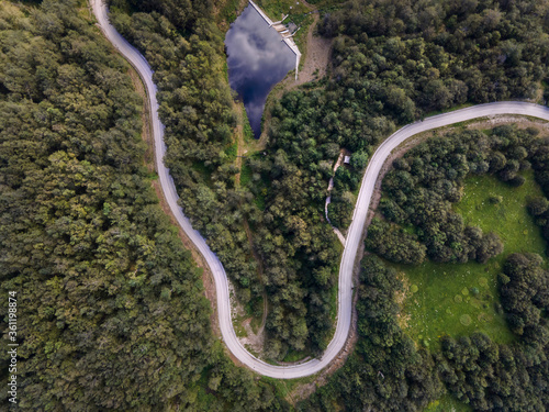 Top down aerial view on road with curves between the forest in nature on mountain range - Drone photo forest and asphalt road travel concept - Stara Planina Old Mountain travel destination in Serbia