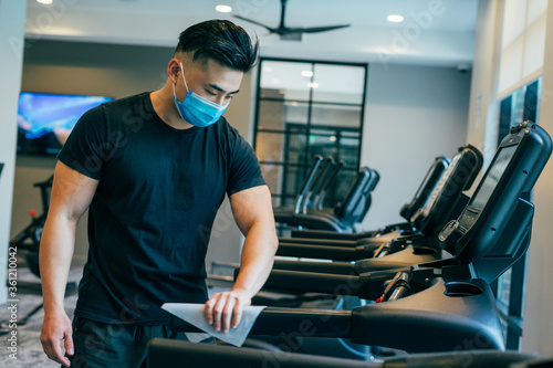 Tablou Canvas Asian male wearing mask during COVID19 wiping down treadmill