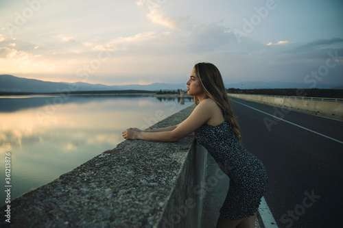 Fotomural Young beautiful rebel woman on empty road at sunset