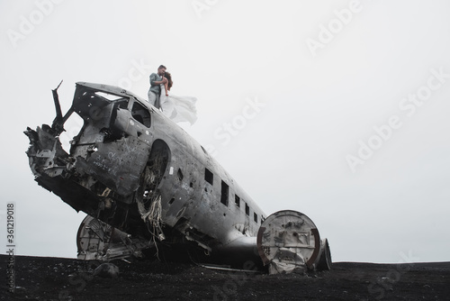young couple holding hands together and coming to the old plane on the ground bl Canvas