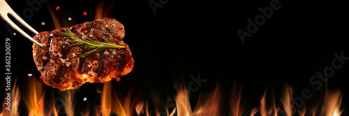 Beef steak falling on the grill with fire. Brazilian barbecue Fototapete